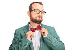 调整他的弓领带的快乐的年轻行家 免版税库存照片