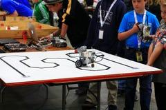 调整他们的机器人的男孩在RoboGames 库存图片