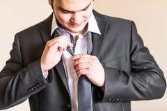 调整他的脖子关系的穿着体面的商人 免版税图库摄影