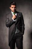 调整他的绿色领带的年轻典雅的人 免版税库存图片