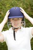 调整盔甲的一名年长女性玩板球者的画象 免版税库存照片
