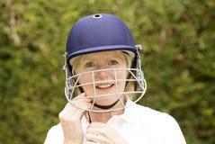 调整盔甲的一名年长女性玩板球者的画象 库存照片