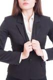 调整衣服夹克的匿名女商人 免版税库存照片
