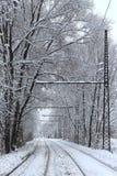 调整轨道、电车线和线在雪 距离的人在电车中止 免版税库存照片