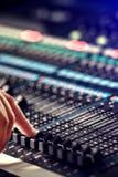 调整音频搅拌器的手指在演播室 免版税库存照片