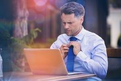 调整领带的英俊的商人,当使用膝上型计算机时 免版税库存图片