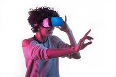 调整VR耳机和感人的空气的妇女 免版税图库摄影