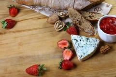谄媚,咸青纹干酪用草莓调味汁,整个五谷面包,在木背景的核桃 与拷贝空间的顶视图 集合 图库摄影