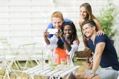 谈一个小组的朋友坐桌和微笑,当ta时 免版税库存照片