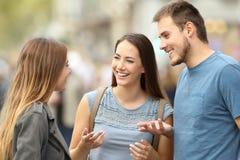 谈三个微笑的朋友站立在街道上 免版税图库摄影