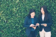 谈两个的商人谈论关于a的信息片剂和笔记 免版税库存照片