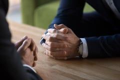 谈判在桌上的两个商人的被扣紧的男性手 库存照片