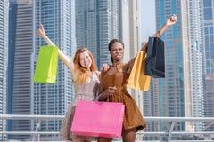 谈判者 举行购物的礼服的两个美丽的女朋友 库存照片