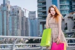 谈判者 拿着购物袋和看在商店的女孩 免版税库存图片