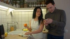谈和使用智能手机的愉快的夫妇,当在家时烹调在厨房里 免版税库存图片