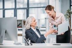 谈和使用膝上型计算机的微笑的女实业家在工作场所 库存图片