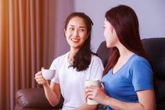 谈和喝一杯咖啡在沙发的两个最好的朋友在 库存照片