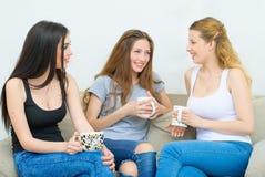 谈和喝咖啡或茶的三个愉快的朋友 免版税库存图片