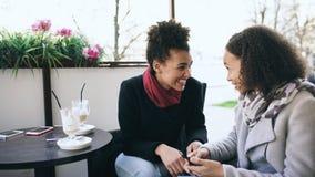 谈和喝在街道咖啡馆的两名可爱的混合的族种妇女咖啡 朋友获得乐趣在参观的购物中心销售以后 图库摄影