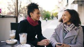 谈和喝在街道咖啡馆的两名可爱的混合的族种妇女咖啡 朋友获得乐趣在参观的购物中心销售以后 免版税库存照片