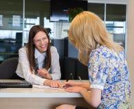 谈和签署信用的两个愉快的女商人 免版税库存图片