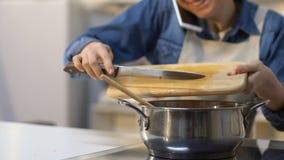 谈微笑的妇女加被切的蕃茄入平底锅,烹调晚餐和电话 股票录像