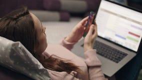 谈手机和在家研究膝上型计算机的妇女 影视素材