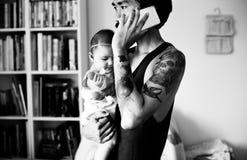 谈的爸爸手机,当运载他的婴孩时 免版税库存照片