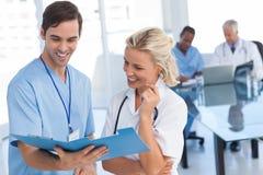 谈论一个蓝色文件的两位微笑的医生 库存照片