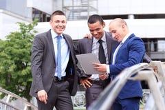 谈论三个的商人文件在办公室外 免版税库存照片