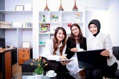 谈论三名年轻的女实业家的幸福他们新的工作 免版税库存照片
