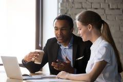 谈论不同的雇员在膝上型计算机附近谈判想法 免版税库存照片