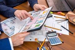 谈论与工程学工具的两个人建筑项目在工作场所 免版税库存图片