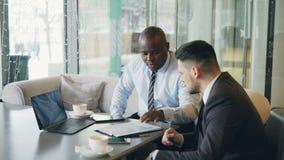谈论两个不同种族的商人看图和图表在膝上型计算机屏幕上和财政报告  股票视频