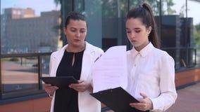 谈论两个企业的女孩步行沿着向下街道和工作计划 慢的行动 股票录像