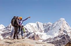 谈论两个的人旅行在指向手的高山击溃 免版税库存照片