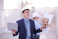 谈论两个的同事数据工作和片剂,膝上型计算机与在建造场所的建筑项目书桌的 免版税图库摄影