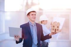 谈论两个的同事数据工作和片剂,膝上型计算机与在建造场所的建筑项目书桌的 免版税库存图片