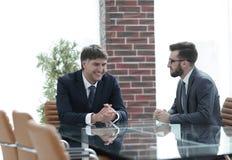 谈论两个的商人坐在办公室桌上的任务 库存图片