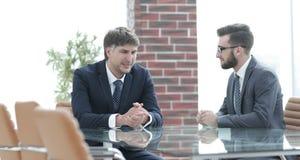 谈论两个的商人坐在办公室桌上的任务 库存照片