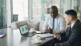 谈论两个确信的商人看图和图表在便携式计算机上和财政报告和 股票视频