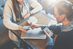 谈论两个年轻的女商人顶视图坐在桌上和经营计划 使用智能手机的妇女 免版税库存照片