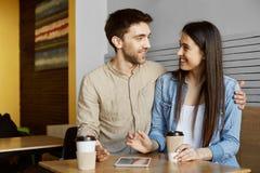 谈论两名时髦的学生愉快的年轻夫妇坐在自助食堂,饮用的咖啡,微笑,拥抱和 免版税库存图片