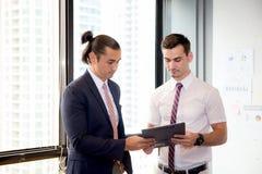 谈论亚裔年轻商人两的人拿着剪贴板和工作 库存照片