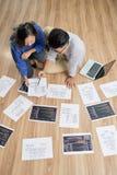 谈论亚裔的设计师在地板上的图 库存照片