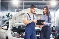 谈论人技工和妇女的顾客修理完成对她的车 图库摄影