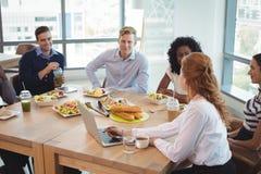 谈论企业的同事,当坐在早餐桌附近时 图库摄影