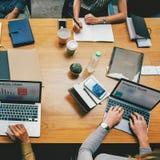 谈论会议的议程在办公室候选会议地点和研究在一张棕色桌上的膝上型计算机的四人 库存图片