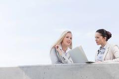 谈论低角度观点的有膝上型计算机的年轻的女实业家,当站立在大阳台反对天空时 免版税库存图片