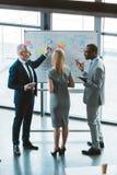 谈论后面观点的专业不同种族的同事企业图和图表 免版税库存图片